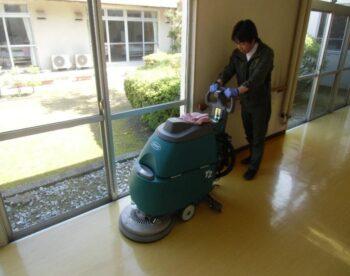 自動床洗浄機を使って床清掃をする社長